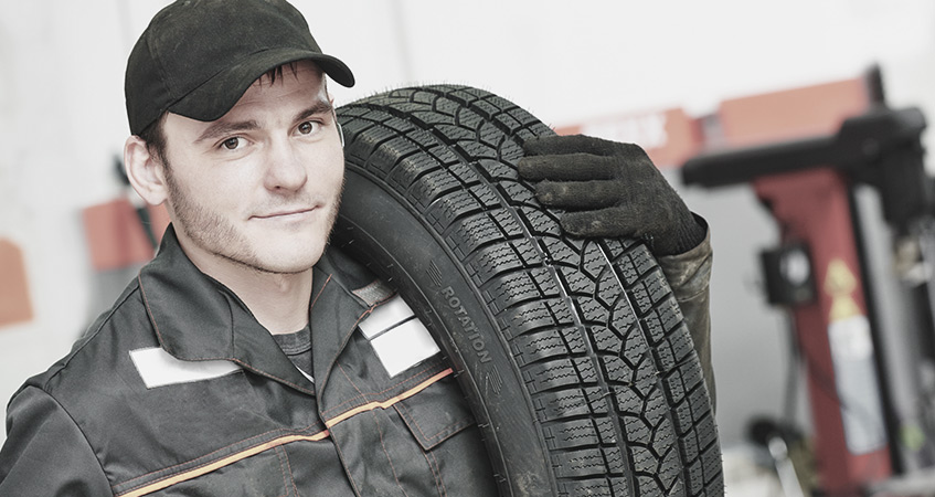 Tyre technician carrying car tyres for fitting - Tyres Nottingham
