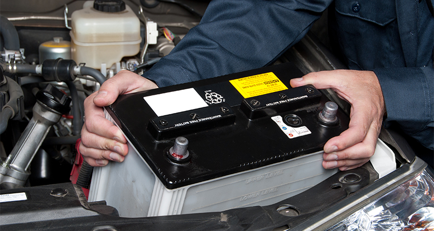 mechainic fitting new car battery, chosen from a range of car batteries